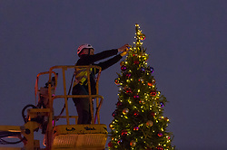 © Licensed to London News Pictures. 03/12/2020. LONDON, UK.  The final decorations are added to the 40 foot Christmas tree at Somerset House ahead of its re-opening after England's second lockdown during the ongoing coronavirus pandemic.  Visitors will also discover pop-up private dining domes in the courtyard forming a new special festive foodie experience.  Photo credit: Stephen Chung/LNP