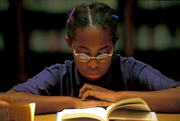 Stock photo of a young elementary student reading a book