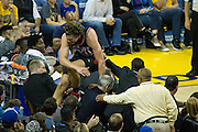 Portland Trail Blazers forward Meyers Leonard (11) leaps over fans to save a loose ball against the Golden State Warriors at Oracle Arena in Oakland, Calif., on October 21, 2016. (Stan Olszewski/Special to S.F. Examiner)