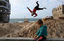 January 2, 2018 - Gaza, Palestinian Territories, Palestine - A Palestinian boy jumps over sand on the beachfront of the al-Shati refugee camp, in Gaza City. (Credit Image: © Majdi Fathi/NurPhoto via ZUMA Press)