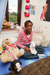Girl in bedroom with soft toys