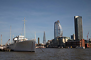 Skyscrapers on the Southern skyline of the River Thames and a ship at high tide in London, England, United Kingdom.