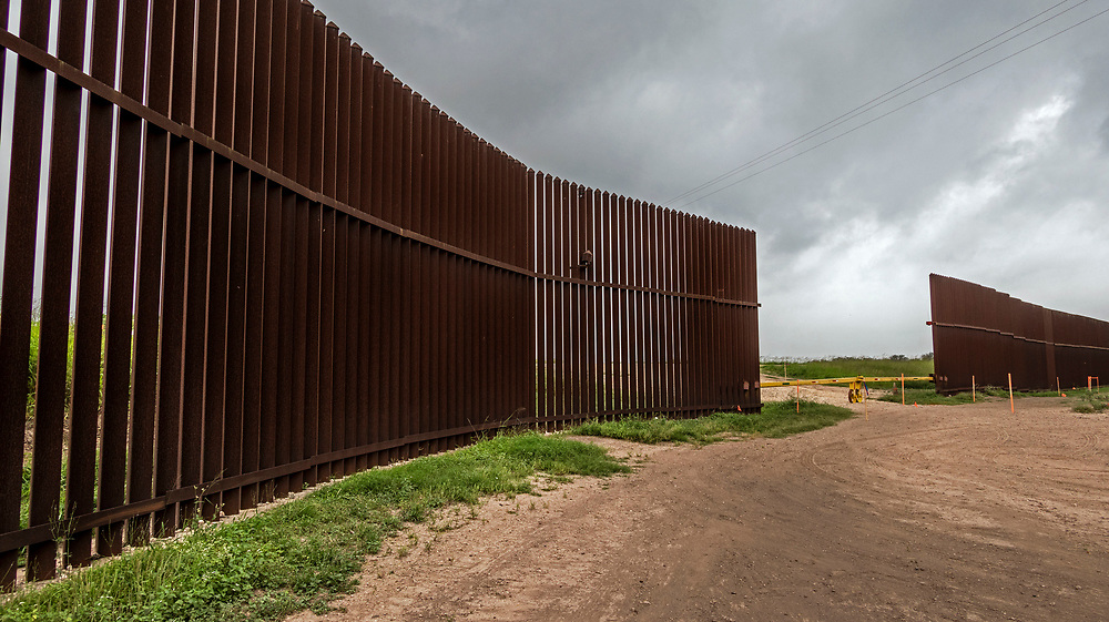 A portion of the steel border fence with make shift barrier, Brownsville Texas, USA. Quite often farmers land is bisected by the fence.