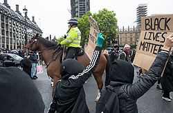 © Licensed to London News Pictures. 06/06/2020. London, UK. Mounted police watch over as protesters gather in Westminster, central London during a Black Lives Matter demonstration over the killing of African American George Floyd. The death of George Floyd, who died after being restrained by a police officer In Minneapolis, Minnesota, caused widespread rioting and looting across the USA. Photo credit: Ben Cawthra/LNP