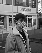Cai Cherry, a resident of Orchard Village, wears a personalised face mask while shopping for essentials at his local shop.