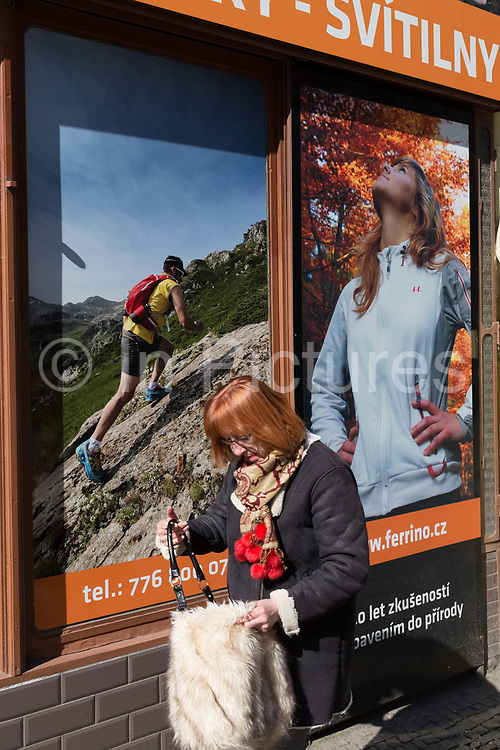 A lady walks past shop banners showing the outdoor lifestyle and well-being in the Holesovice district, Prague 7, on 20th March, 2018, in Prague, the Czech Republic.