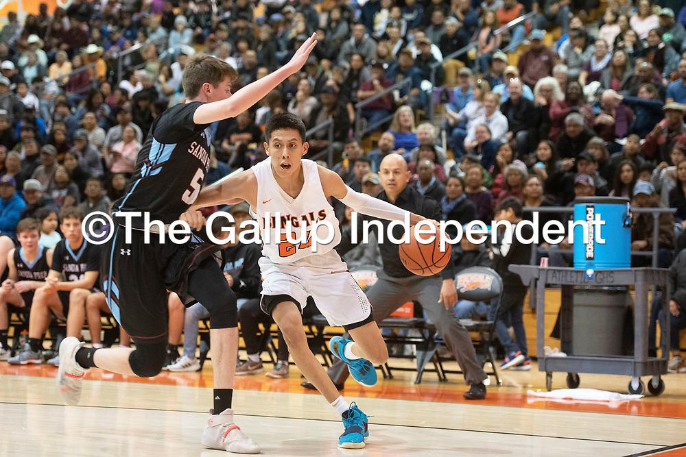 Gallup's Quinn Atazhoon (24) dribbles as Sandia Prep's Sam Henderson (5) defends Friday night at the Gallup Invitational boys basketball tournament at Gallup High School. Gallup beat Sandia Prep 61-60.
