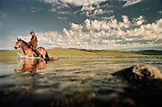 A horse man crosses the Arkhangai river close to Tsetserleg, in Central Mongolia. Mongolians learn to horse ride before they can even walk, they are expert hose riders...