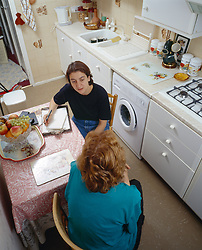 Haringey housing officer and tenant in discussion in tenant's kitchen London UK