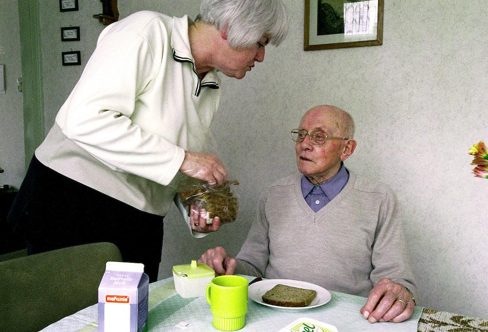 NL - Leiden, voorj.2000.Gezinsverzorgster/ouderen verzorgster bij een bejaarde man. Ze heeft hem geholpen met wassen, het huishouden en heeft nu de lunch boterham voor hem klaargezet.  Zo kan de oude man toch thuis blijven wonen, ipv in het bejaardenhuis...Foto (c) Michiel Wijnbergh/Hollandse Hoogte