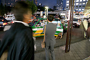 businesspeople entering and waiting for taxi in front of Shinagawa station Tokyo