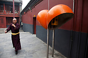 "Monks walk past a telephone booths at Yonghe Temple, also known as the ""Palace of Peace and Harmony Lama Temple"", the ""Yonghe Lamasery"", or - popularly - the ""Lama Temple"" is a temple and monastery of the Geluk School of Tibetan Buddhism located in the northeastern part of Beijing, China. It is one of the largest and most important Tibetan Buddhist monasteries in the world. The building and the artworks of the temple is a combination of Han Chinese and Tibetan styles."