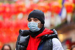 © Licensed to London News Pictures. 26/01/2020. London, UK.  A man in Chinatown in central London is seen wearing a face mask following the outbreak of Coronavirus in China which has killed 41 people. Photo credit: Dinendra Haria/LNP