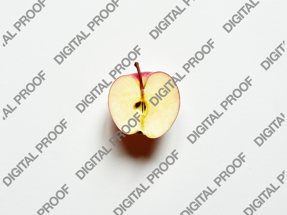 Red apple sliced by half isolated in studio over a bright white background