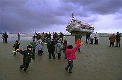 """BLANKENBERGE, BELGIUM - NOVEMBER 9, 2001 -  School children play on the beach as storm clouds roll in, seemingly oblivious to the German cargo ship """"Heinrich Behrmann"""", which was beached by heavy seas after losing power to the main engine late Thursday night at Blankenberge. The ship was heading for the port at Zeebrugge from Ireland, and was carrying dry cargo, none of which was hazardous. Unie Van Redding - En Sleepdienst N.V. was hired to free the ship. Three unsuccessful attempts were made Friday, the second attempt resulted in the injury of two workers when tug boat cables snapped. The beached ship has attracted the attention of curious tourists. (Photo © Jock Fistick)"""