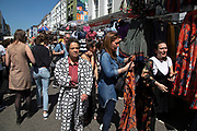Local character wearing an patterned zoot suit at Portobello Road Market in Notting Hill, West London, England, United Kingdom. People enjoying a sunny day out hanging out at the famous Sunday market, when the antique stalls line the street.  Portobello Market is the worlds largest antiques market with over 1,000 dealers selling every kind of antique and collectible. Visitors flock from all over the world to walk along one of Londons best loved streets.