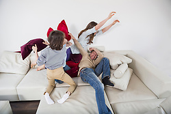 Family doing pillow fight on couch