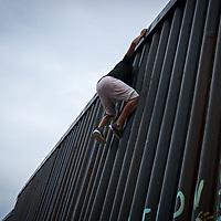 Olman Paz, from Progreso, Yoro, Honduras, climbs the wall that divides the US and Mexico at the Tijuana border.