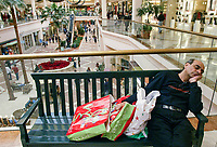 Ravi Jagasia, of Singapore, gets a few winks at Sherman Oaks Fashion Square Monday afternoon. He flew in Tuesday to visit family and holiday shopping wore him out, he said. Malls are swamped with last minute shoppers as Christmas approaches.