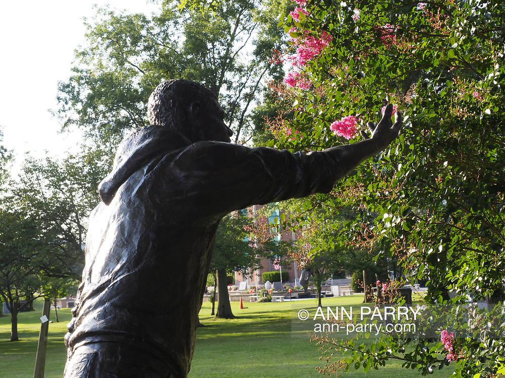 East Meadow, New York, USA. Summer 2017. Drunk driving monument statue at Eisenhower Park pond area, with Nassau County Eisenhower Park September 11, 2001 Memorial on west side of pond and War Memorials on east side of pond.