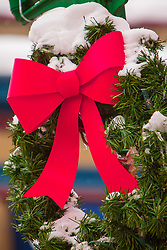 Washington, Leavenworth, Christmas wreath with red bow in snow