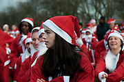 Victoria Park , East London. December 8th 2013, Santa Run in aid of different charities, organised by 'Doitforcharity'. pre run warm-up exercises