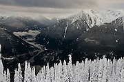 Trees stand covered in heavy snow on Sourdough Ridge, North Cascades National Park, Washington. Diablo Lake is visible in the valley below.