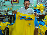 01 DECEMBER 2015 - BANGKOK, THAILAND: Workers sew yellow shirts in family owned workshop that makes yellow shirts to be sold during the King's Birthday. This shop was contracted to make 14,000 yellow shirts and was paid 18 Baht (about 0.55¢ US) each for the shirts which will sell for about 250 Baht (about $6.90 US). Hundreds of small clothing shops in Bangkok make yellow tee shirts and sports shirts in November and December before the King's Birthday. People wear yellow at events associated with the King because he was born on a Monday, and yellow is Monday's color in Thai culture. It's also the color of the monarchy. Bhumibol Adulyadej, the King of Thailand, was born 5 December 1927 and has reigned since9 June 1946, he is the world's longest-serving current head of state and the longest-reigning monarch in Thai history. He is widely revered throughout Thailand and his birthday is a national holiday.      PHOTO BY JACK KURTZ