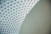 Interior view of the Great Court in The British Museum, London. A Modern highly architectural glass lattice roof covers the entire area. A hand points.