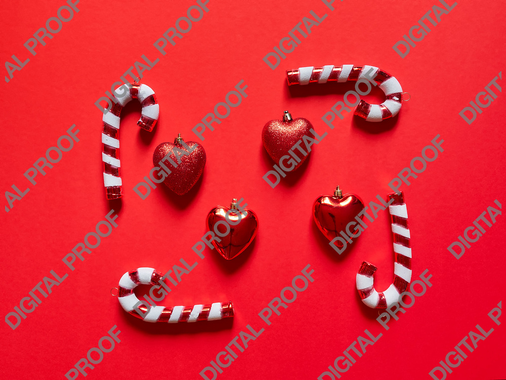 Christmas candy cane and hearts at studio above view over a red background isolated flatlay