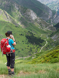 Woman hiker talking on mobile phone in the High Pyrenees, Gavarnie, France