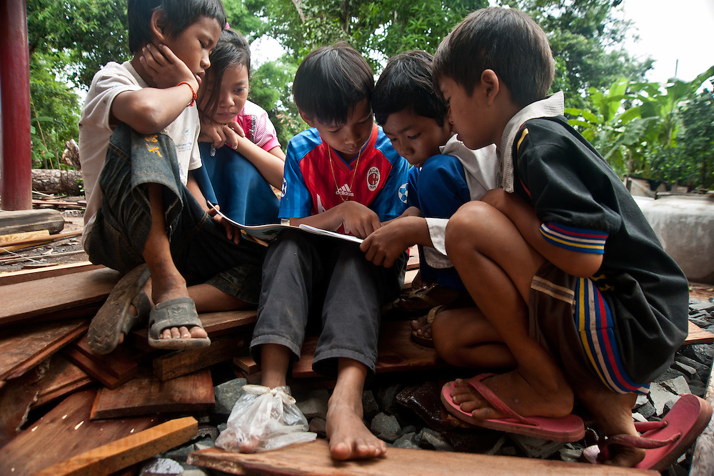 """Chheu Teal Korng village:.Remarkable how much CWS has accomplished here in less than a.year, because they are working with such a willing and committed local committee. Kindergarten for 21 students in village.  Teacher is 18 year old Nen Sras who said, """"These children grow up so far from everything.  With this.Kindergarten I can at least give them a headstart for primary.school."""" Boy with red sports shirt, reading to friends is Rin Daro (11).reading to some of the younger kids."""