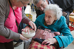 Visually impaired people with carers on outing to Denby Pottery. Feeling unglazed bowl.