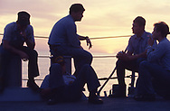 Smoke break, Members f the crew of the USS Hart at dusk in the Red Sea in November 1990. Photograph ny Dennis Brack. bb78