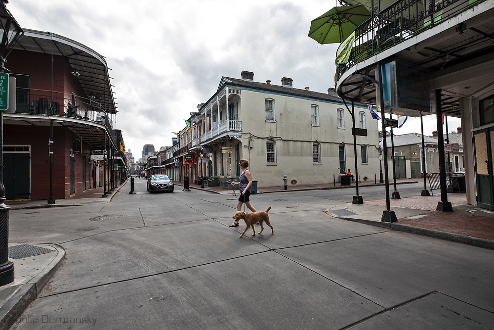 A woman walking a dog in New Orleans French Quarter on March 27, 2020  during a mandatory stay at home order due to the COVID-19 Pandemic. New Orleans , major city, USA