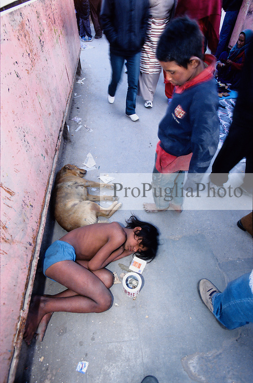 A young man 'sleeping' on the pavement of a busy crossing point in Kathmandu.