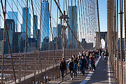 Tourists and local people stroll across Brooklyn Bridge from Manhattan, New York City