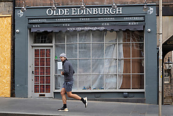 Edinburgh, Scotland, UK. 29 April 2020. Views of Edinburgh Old Town as coronavirus lockdown continues in Scotland. Streets remain deserted and shops and restaurants closed and many boarded up. Scottish Government now recommends public to wear face masks. Pictured; male jogger runs past closed down tourist shop on Royal Mile. Iain Masterton/Alamy Live News