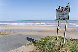 Road abruptly ending at eroded cliff edge; with warning sign; at Tunstall; East Yorkshire; England