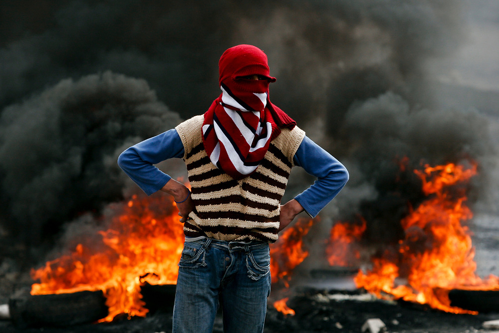 A Palestinian youth with his face covered stands in front of burning tires after clashes between Palestinians and Israeli border police erupted in the West Bank refugee camp of Shuafat, in East Jerusalem, on March 3, 2008. Clashes broke out across the West Bank on Monday between Israeli troops and Palestinian youths protesting Israel's Gaza operations.
