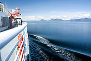 USA, Alaska, A photographer takes in the scenic views from the deck of a Alaska State ferry along the Inside Passage in Southeast Alaska.