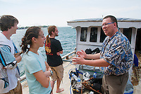 Professor Hinrich Kaiser speaks to students Eric Leatham, Caitlin Sanchez, and Scott Heacox on a boat in the harbor at Dili, Timor-Leste (East Timor)