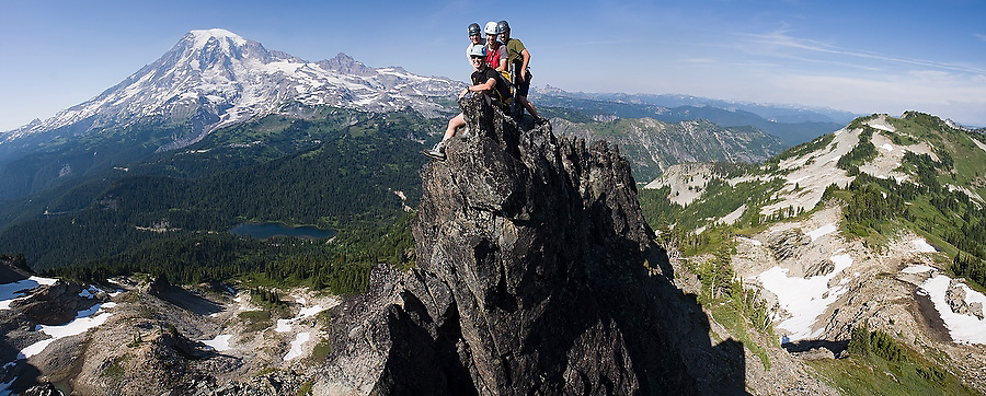 Climbers crowd onto the narrow summit of Castle Peak for a group shot during the traverse of the Tatoosh Range in Mount Rainier National Park, Washington.