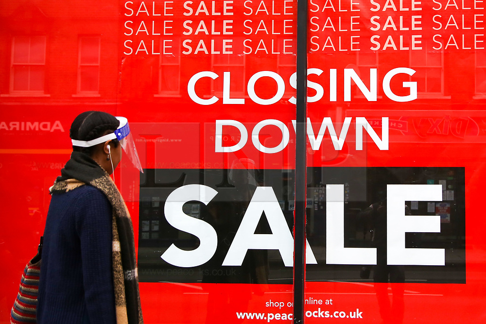 © Licensed to London News Pictures. 13/10/2020. London, UK. A woman wearing a face shield walks past a 'Closing Down Sale' window display in a Peacock store in north London. Edinburgh Woollen Mill, owner of the Peacocks and Jaeger clothing brands has appointed administrators in an attempt to save the business, putting 21,000 jobs at risk due to lack of sales following the COVID-19 lockdown. According to the Edinburgh Woollen Mill, there are allegations, that the retailer and several rivals failed to pay some Bangladeshi suppliers during the coronavirus lockdown in an attempt to cut costs for clothes they were unlikely to sell.Photo credit: Dinendra Haria/LNP