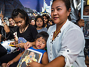 14 OCTOBER 2016 - BANGKOK, THAILAND: A woman and her daughter wait on Rajadamnoen Avenue in Bangkok for the King's body to be brought to the Grand Palace. The weather in Bangkok was very hot Friday and several people were overcome by the heat and humidity. King Bhumibol Adulyadej died Oct. 13, 2016. He was 88. His death comes after a period of failing health. With the king's death, the world's longest-reigning monarch is Queen Elizabeth II, who ascended to the British throne in 1952. Bhumibol Adulyadej, was born in Cambridge, MA, on 5 December 1927. He was the ninth monarch of Thailand from the Chakri Dynasty and is known as Rama IX. He became King on June 9, 1946 and served as King of Thailand for 70 years, 126 days. He was, at the time of his death, the world's longest-serving head of state and the longest-reigning monarch in Thai history.     PHOTO BY JACK KURTZ