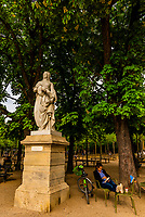 Woman relaxing next to a statue of Anne Marie Louise D'Orleans, Duchesse of Montpensier (1627-1695), Luxembourg Gardens, Paris, France.