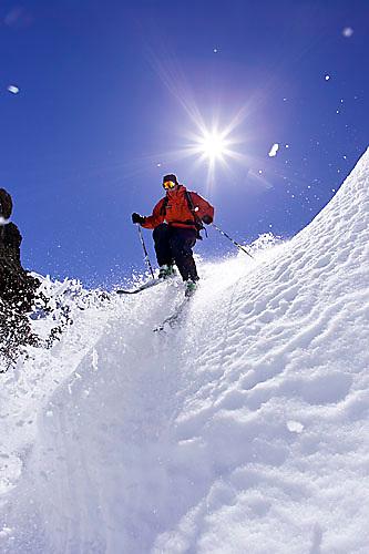 Young man dropping into couloir at Kirkwood ski resort near Lake Tahoe, CA.