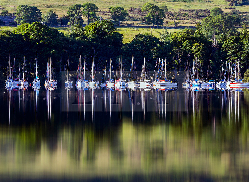 © Licensed to London News Pictures. 29/06/2018. Pooley Bridge UK. The moored boats at Ullswater Yacht club near Pooley Bridge reflect in to the calm water of Ullswater lake in Cumbria this morning. Photo credit: Andrew McCaren/LNP
