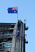 Huge Australian Flag at top of the arch of the Sydney Harbour Bridge. A groups of tourists can be seen climbing the bridge. Sydney, Australia
