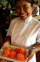 Thai cook proudly displaying her beautifully carved vegetables.  As with most world-class cuisines, the presentation of the food is almost as important as its taste and preparation.  A beautiful Thai smile doesn't hurt in the presentation either.